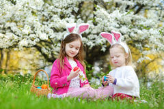 Two adorable little sisters playing with Easter eggs on Easter day Stock Photo