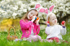 Two adorable little sisters playing with Easter eggs on Easter day Stock Images