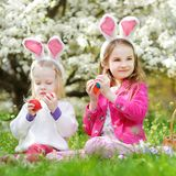 Two adorable little sisters playing with Easter eggs on Easter day Royalty Free Stock Photography