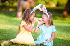 Two adorable little sisters playing with eggs wearing bunny ears on Easter day Stock Photo