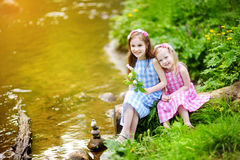 Two adorable little sisters playing by a river in sunny park Stock Photography