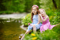 Two adorable little sisters playing by a river in sunny park on a beautiful summer day Stock Photo