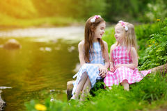 Two adorable little sisters playing by a river in sunny park on a beautiful summer day Royalty Free Stock Photography