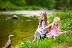 Two adorable little sisters playing by a river in sunny park on a beautiful summer day Stock Images