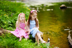 Two adorable little sisters playing by a river in sunny park on a beautiful summer day Royalty Free Stock Images