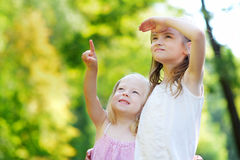 Two adorable little sisters pointing at a plane on the sky Royalty Free Stock Photos