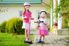 Two adorable little sisters riding their scooters Royalty Free Stock Photo
