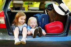 Two adorable little sisters sitting in a car Royalty Free Stock Photos