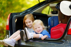Two adorable little sisters sitting in a car Stock Photos
