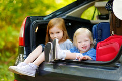 Two adorable little sisters sitting in a car Royalty Free Stock Image