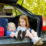 Two adorable little sisters sitting in a car Royalty Free Stock Images