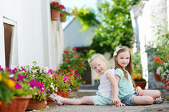 Two adorable little sisters sitting among flowers Stock Photo