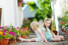 Two adorable little sisters sitting among flowers Royalty Free Stock Photo