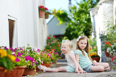 Two adorable little sisters sitting among flowers Stock Photography