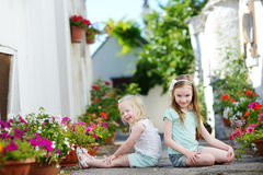 Two adorable little sisters sitting among flowers pots on warm and sunny summer day Stock Photo