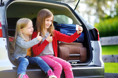 Two adorable little sisters taking photo of themself before going on vacations with their parents. Two kids looking forward for a road trip or travel Stock Image