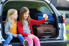 Two adorable little sisters taking photo of themselves before going on vacations with their parents. Two kids sitting in a car ready to travel. Active leisure Royalty Free Stock Photos