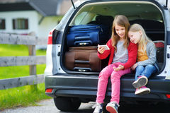 Two adorable little sisters taking photo of themselves before going on vacations with their parents. Two kids sitting in a car ready to travel. Active leisure Stock Images