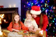 Two adorable little sisters and their mother baking Christmas cookies by a fireplace Stock Photography