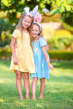 Two adorable little sisters wearing bunny ears on Easter day outdoors Royalty Free Stock Photo