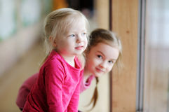 Two adorable little sisters by the window Royalty Free Stock Photography