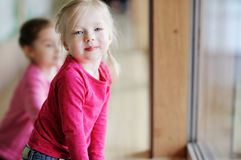 Two adorable little sisters by the window Stock Images
