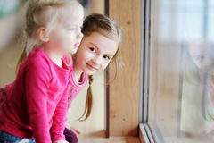 Two adorable little sisters by the window Stock Photo