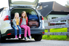 Two adorable little sitting in a car before going on vacations with their parents Royalty Free Stock Image