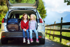 Two adorable little sitting in a car before going on vacations with their parents. Two kids looking forward for a road trip or travel Royalty Free Stock Photo