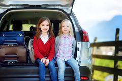 Two adorable little sitting in a car before going on vacations with their parents. Two kids looking forward for a road trip or travel Royalty Free Stock Image