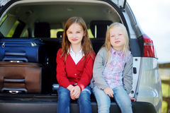 Two adorable little sitting in a car before going on vacations with their parents. Two kids looking forward for a road trip or travel Royalty Free Stock Photos