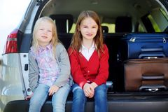 Two adorable little sitting in a car before going on vacations with their parents. Two kids looking forward for a road trip or travel Stock Images