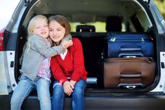 Two adorable little sitting in a car before going on vacations with their parents Royalty Free Stock Photos