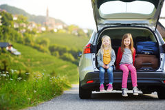 Two adorable little sitting in a car before going on vacations with their parents. Two kids looking forward for a road trip or travel Royalty Free Stock Images