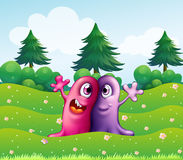 Two adorable one-eyed monsters near the pine trees Royalty Free Stock Photos