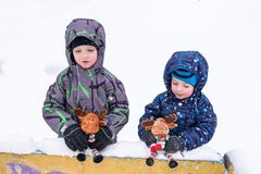 Two adorable preschool kids brother boys in winter wear sit amou Stock Image