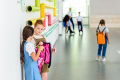 two adorable schoolgirls chatting at school corridor stock photos
