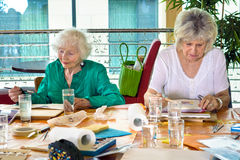 Two adorable senior women painting at table Stock Photography
