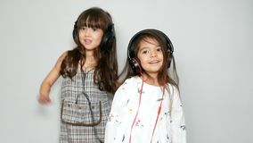 Two adorable sister mixed race girl enjoy with music and dancing with headphones. leisure activities stock video