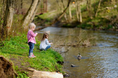 Two adorable sisters feeding ducks by a river Royalty Free Stock Images