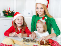 Two adorable sisters with her mother baking Christmas cookies Stock Photo