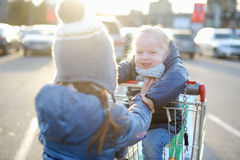Two adorable sisters playing with a shopping cart Stock Images