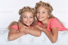 Two adorable twin sisters in beautiful pink dresses. With modern hairstyles posing at home royalty free stock photo