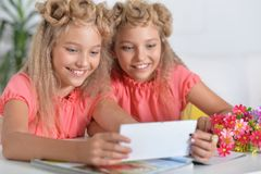 Two adorable twin sisters in beautiful pink dresses. Using smartphone royalty free stock photos