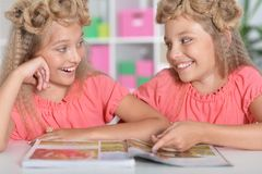 Two adorable twin sisters with modern hairstyles. Reading magazine royalty free stock images