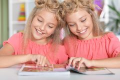 Two adorable twin sisters with modern hairstyles. Reading magazine stock images