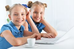 Two adorable twin sisters. Using laptop at home royalty free stock image