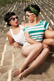 Two adorable women with tattoos wearing sunglasses Stock Photo