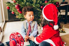 Two adorable 3 year old kids playing by the Christmas tree royalty free stock photography