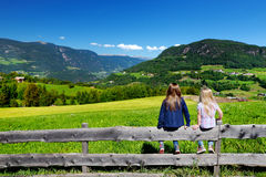 Two adorables little sisters admiring beautiful landscape of Dolomites mountain range, South Tyrol, Italy Royalty Free Stock Photos